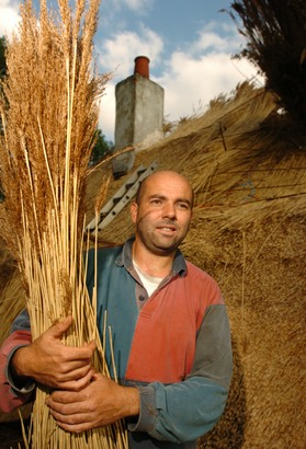 Andrew Rees holding a buch of water reed in front of a roof under construction in Ashdon, Essex